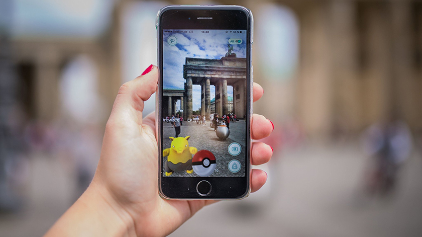 A woman points her smart phone at the Brandenburg Gate as she plays the Pokemon Go